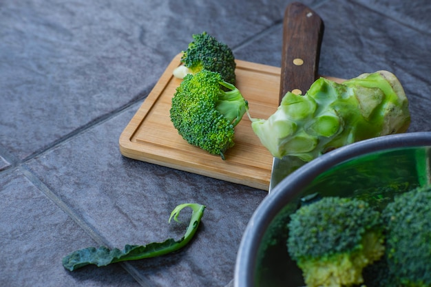 Brócolis cru cortado em uma tábua de madeira