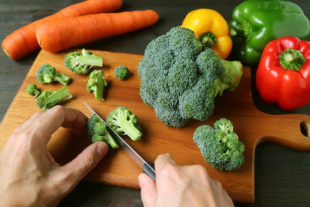 Brócolis de corte de mão do homem na tábua de madeira com legumes coloridos embaçados