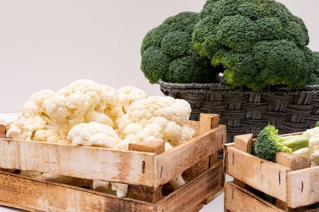 Brócolis e couve-flor em caixa de madeira e brócolis na cesta