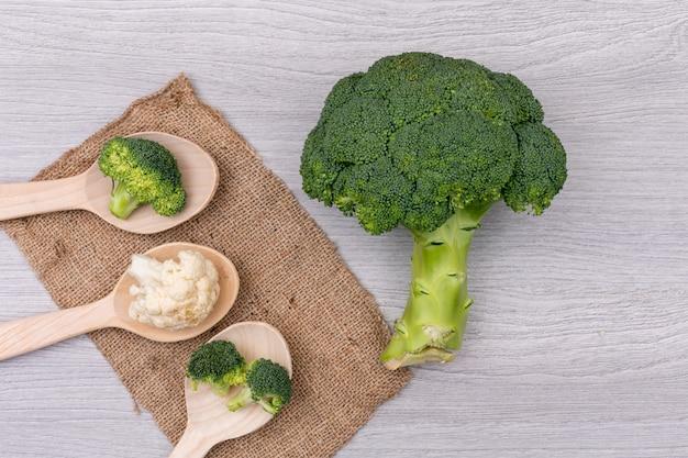 Brócolis e couve-flor em colheres de madeira em pano de saco branco mesa de legumes frescos
