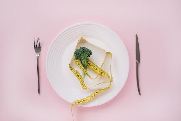 Brócolis e fita de medição em um prato