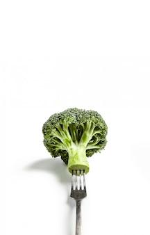 Brócolis em um garfo em um branco