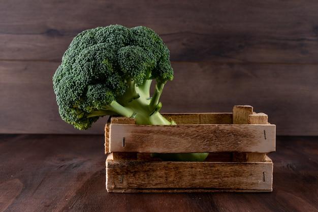 Brócolis em um vegetal fresco de caixa de madeira na superfície de madeira