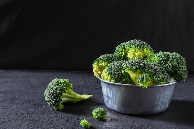 Brócolis em uma tigela sobre um fundo preto.