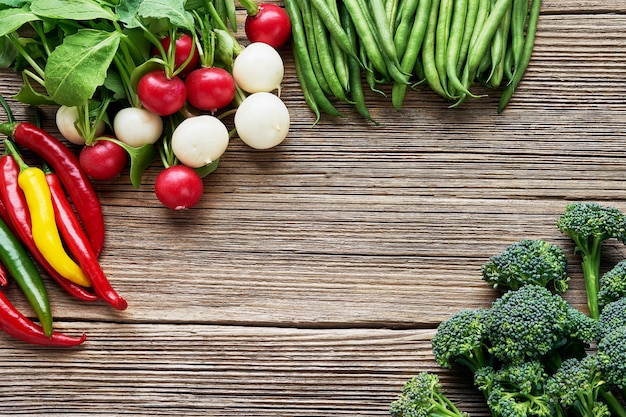 Brócolis, feijão verde, rabanete colorido e pimenta malagueta em fundo de madeira rústica