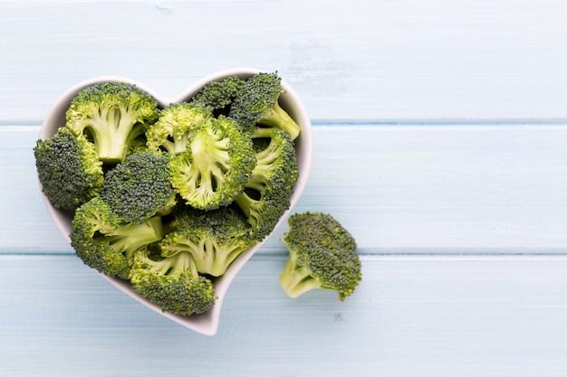 Brócolis fresco em uma tigela em forma de coração em um fundo de madeira.