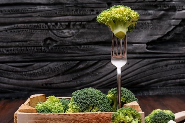 Brócolis fresco na caixa de madeira e no garfo