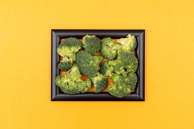 Brócolis fresco no quadro preto na superfície amarela