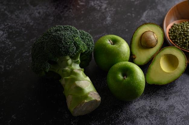 Brócolis, maçã e abacate em um piso de cimento preto.