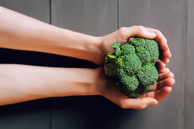 Brócolis nas mãos. uma superfície de madeira. conceito de alimentação saudável.