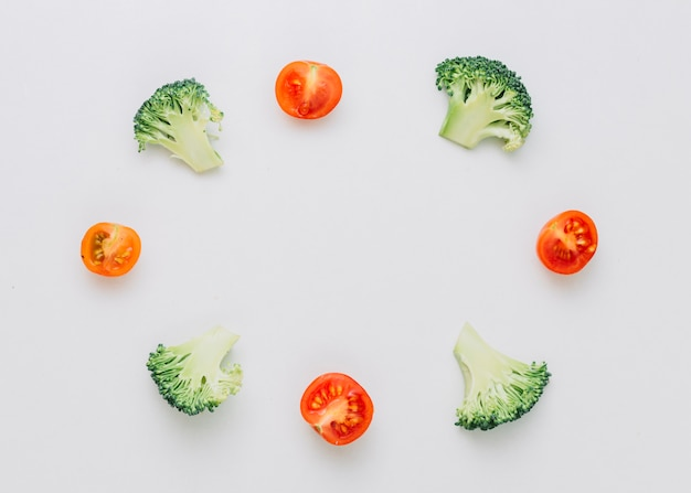 Brócolis pela metade arranjados e tomates cereja no quadro circular isolado no fundo branco