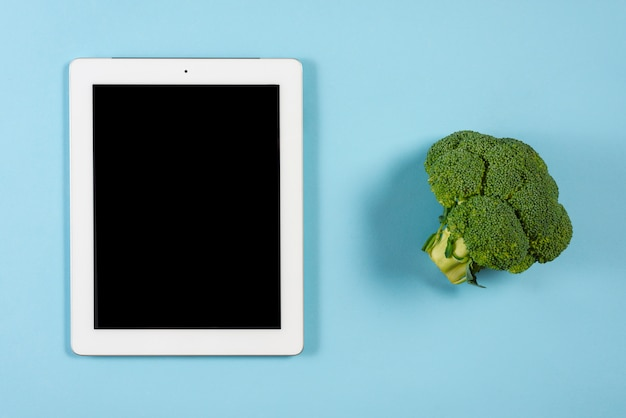 Brócolis perto do tablet digital com tela preta no pano de fundo azul