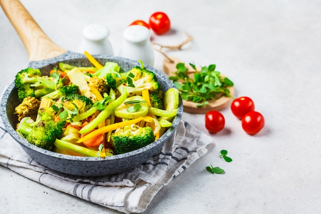 Brócolis, pimentas, milho, abobrinha e tomates fritados na bandeja em um fundo branco.