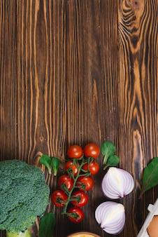 Brócolis; tomate cereja; cebola cortada ao meio e espinafre na mesa