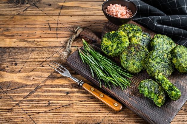 Brócolis vegetariano assado e rissol ou costeleta de vegetais de ervilha, falafel. fundo de madeira. vista do topo. copie o espaço.