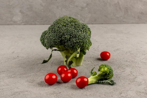 Brócolis verde vista frontal maduro fresco junto com vermelho tomate cereja isolado na mesa escura