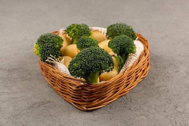 Brócolis verde vista superior, juntamente com batatas dentro da cesta no chão cinza