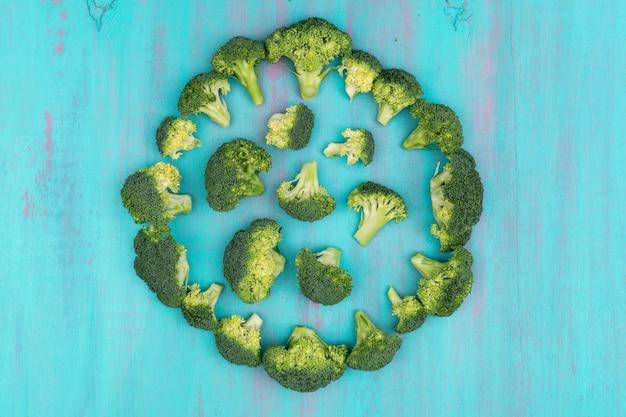 Brócolis vista superior dispostas circular na superfície de madeira azul