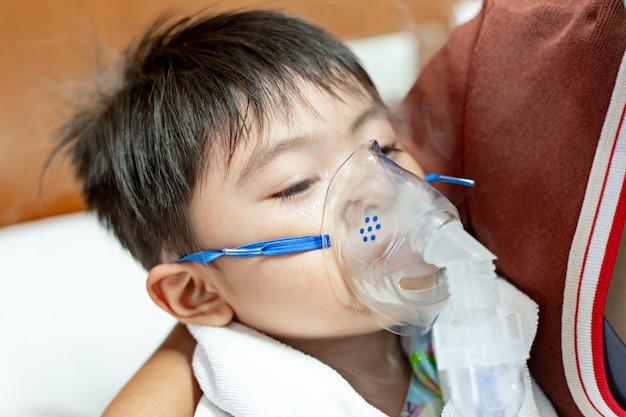 Broncodilatador é uma substância que dilata os brônquios e bronquíolos, diminuindo a resistência nas vias respiratórias e aumentando o fluxo de ar para o pulmão. mãe está usando broncodilatador para menino asiático