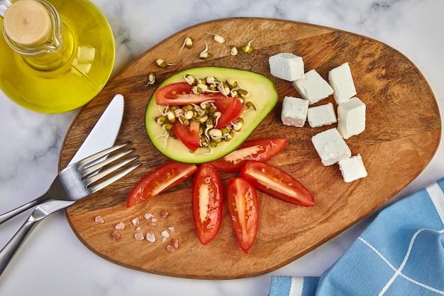 Brotos de feijão mungo, abacate, fatias de tomate, queijo feta, azeite, talheres e um pano de prato em uma placa de madeira