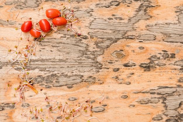 Brotos e tomates no cenário texturizado de madeira