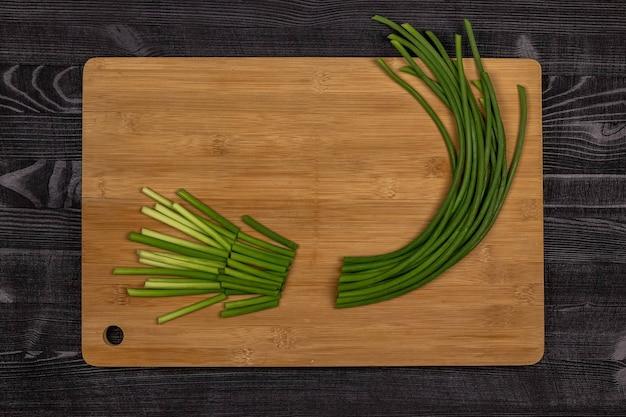 Brotos verdes de alho ou lanças de alho em uma placa de corte preparada para corte como parte do processo de fabricação de pasta de alho ou para posterior congelamento. vista do topo