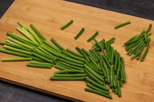 Brotos verdes de alho ou lanças de alho em uma placa de corte preparada para corte como parte do processo de fabricação de pasta de alho ou para posterior congelamento