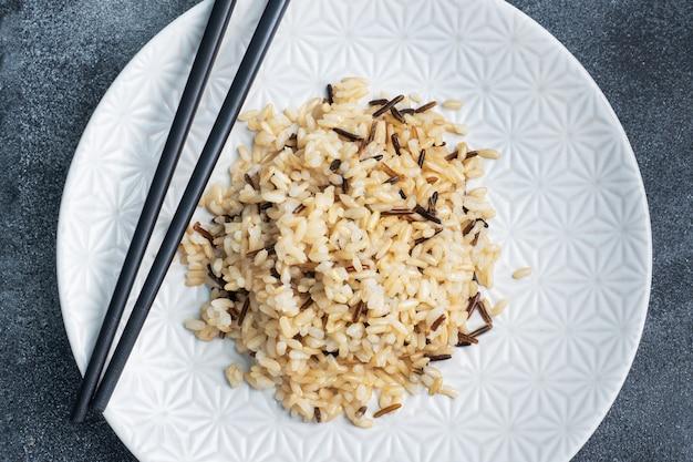 Brown e arroz com casca em um prato com pauzinhos.