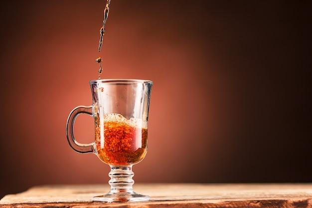 Brown espirra a bebida da xícara de chá em uma parede marrom