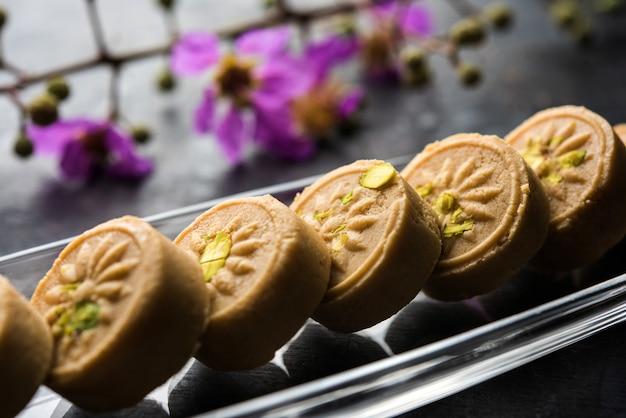 Brown pera ou pedha é um doce indiano feito com khoa, açúcar e condimentos tradicionais, incluindo sementes de cardamomo e nozes de pistache. servido em uma tigela ou prato. foco seletivo