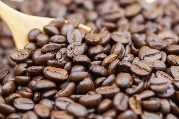 Brown roasted a textura dos feijões de café com fundo de madeira da colher.