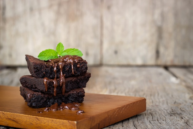 Brownie caseiro servido com fudge de chocolate. sobremesa doce em fundo de madeira.