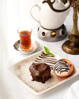 Brownie com calda de chocolate, servido com sorvete de baunilha e chá preto