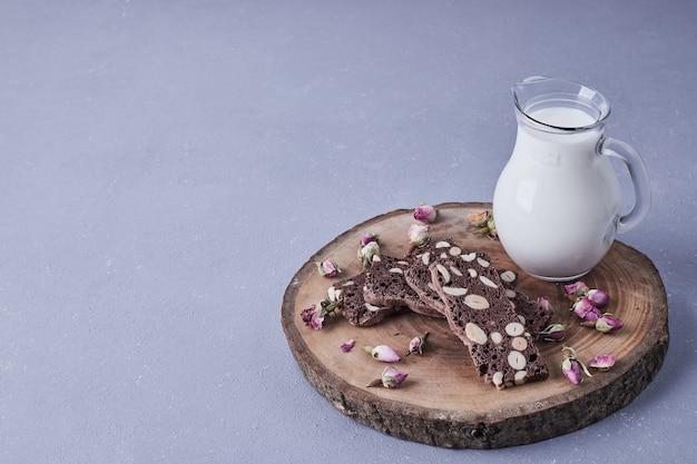 Brownie com nozes servido com um pote de leite.