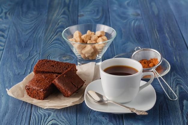 Brownie de chocolate num prato branco. uma xícara de café e um garfo na mesa de madeira azul