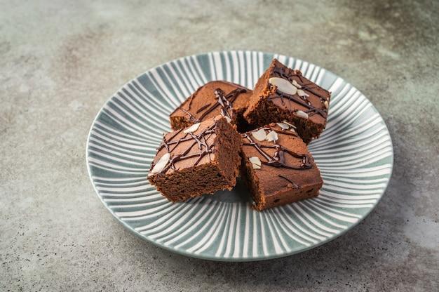 Brownies caseiros com pétalas de amêndoa em uma placa texturizada em um fundo de madeira.