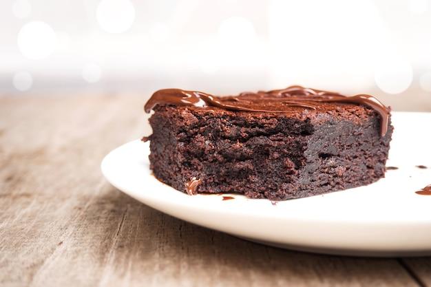 Brownies caseiros no prato branco. com cobertura de fudge de chocolate. sobre fundo de madeira.