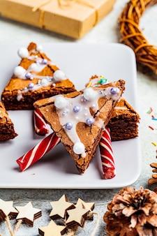 Brownies da árvore de natal com bastão de doces e crosta de gelo, fundo cinzento. conceito de comida de natal.
