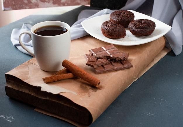 Brownies de cacau, barras de chocolate e uma xícara de chá.