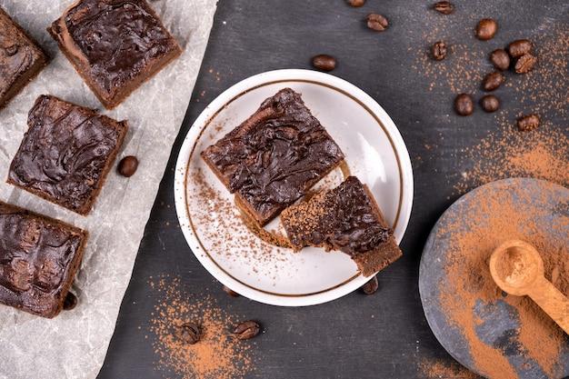 Brownies de cacau com chocolate preto derretido cortados em pedaços quadrados. vista superior plana lay