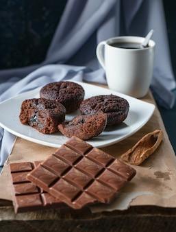 Brownies de cacau e barras de chocolate com uma xícara de chá