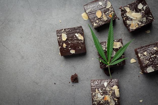 Brownies de cannabis e folhas de cannabis colocados no chão escuro