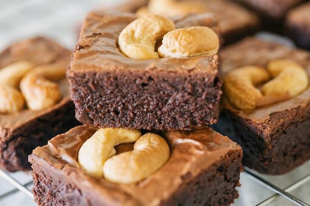 Brownies de caramelo escuro cozido fresco com cobertura de castanha de caju na cremalheira em close-up vista. delicioso sabor amargo doce, em borracha e fudgy. brownie é um tipo de bolo de chocolate. conceito de padaria caseira