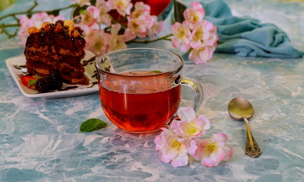 Brownies de chocolate caseiros e xícara de chá no fundo de mármore, foco seletivo