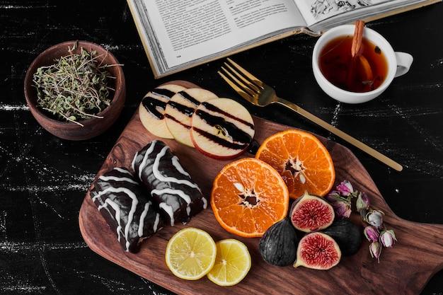 Brownies de chocolate com frutas cítricas e xícara de chá.