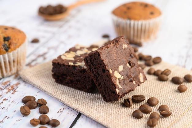 Brownies de chocolate de saco e grãos de café em uma mesa de madeira.