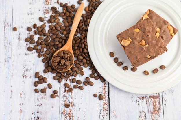 Brownies de chocolate em um prato branco e grãos de café em uma colher de pau.
