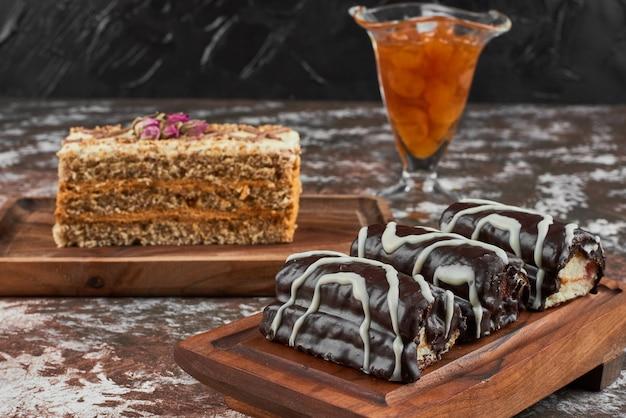 Brownies e bolo de cenoura em uma placa de madeira.