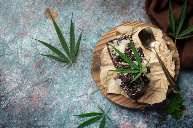 Brownies e folhas de cannabis colocados em uma tábua de madeira