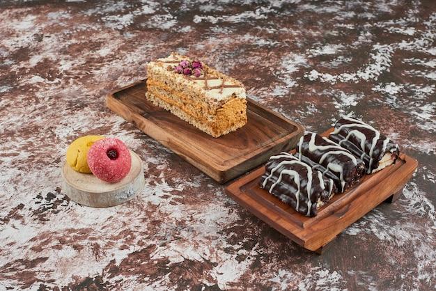 Brownies e uma fatia de bolo em um pedaço de madeira.